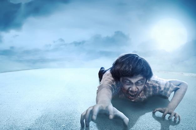 Страшные зомби с кровью и раной на теле ползут по асфальтированной дороге