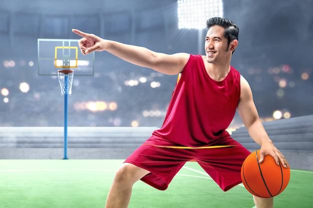 アジア人のバスケットボール選手がボールをドリブル