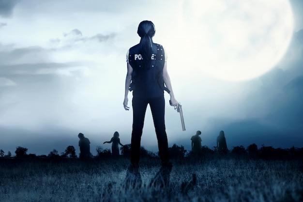 彼女の手に銃を持つアジアの警官の背面図は芝生のフィールドでゾンビに直面します。