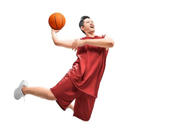 アジア人のバスケットボール選手がボールで空中ジャンプします。