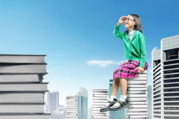 眼鏡の本の山の上に座って、楽しみにしてアジアのかわいい女の子