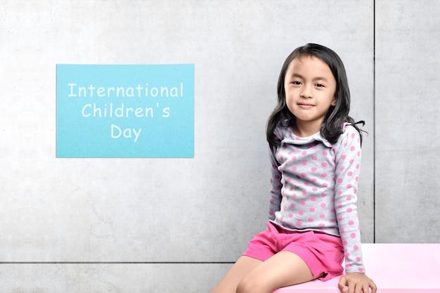 灰色の壁と机の上に座っているアジアのかわいい女の子