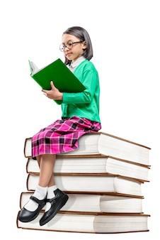 本の山の上に座って、本を読んでメガネでアジアのかわいい女の子