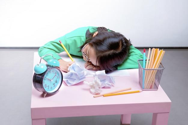 メガネでアジアのかわいい女の子が机の上に書きながら眠りに落ちる