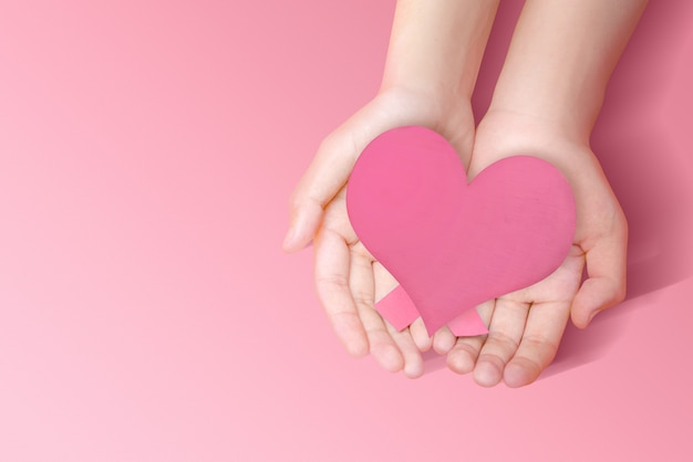 ピンクのハートを示す人間の手