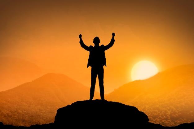 Силуэт деловой человек, стоящий на вершине горы