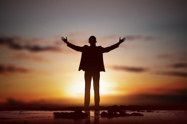 ビジネスマンのシルエットが手を上げ、神に祈る
