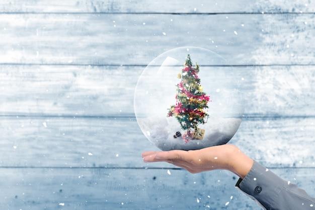 カラフルなライトとガラス玉飾りの装飾品で飾られたクリスマスツリーを保持している人間の手