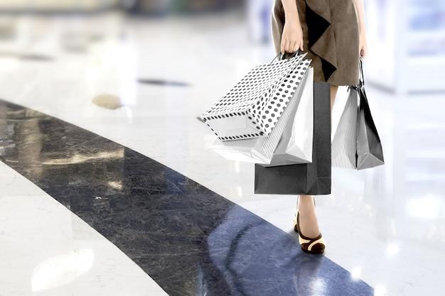 ショッピングモールで買い物袋を運ぶ女性