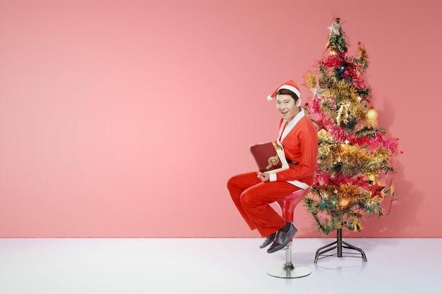 座っているとカラフルなライトや装飾品で飾られたクリスマスツリーとギフトボックスを保持しているサンタ衣装でアジア人