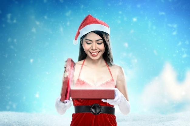 ギフト用の箱を開くサンタ衣装でアジアの女性