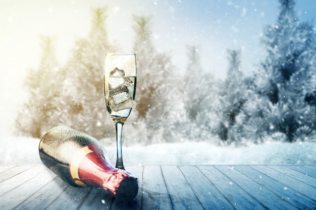シャンパンボトルと木製のテーブルの上のガラス