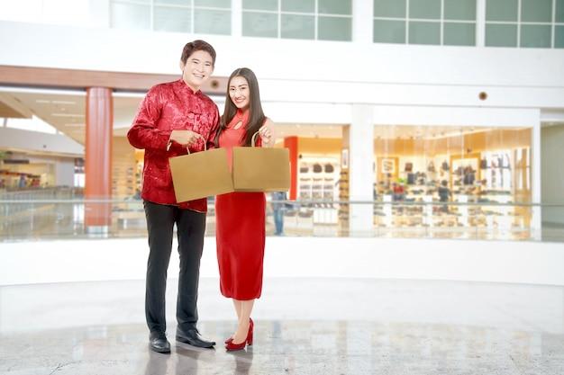 ショッピングバッグを保持しているチャイナドレスのアジアの中国のカップル