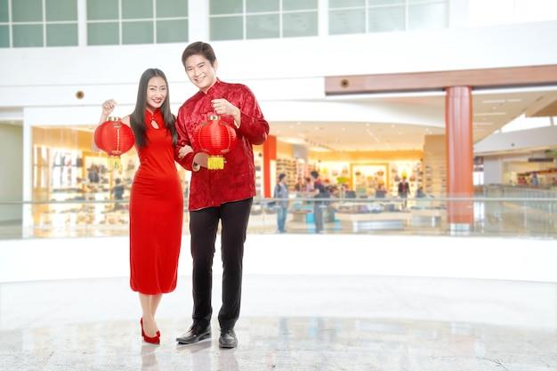 中国のランタンを保持しているチャイナドレスのアジアの中国のカップル