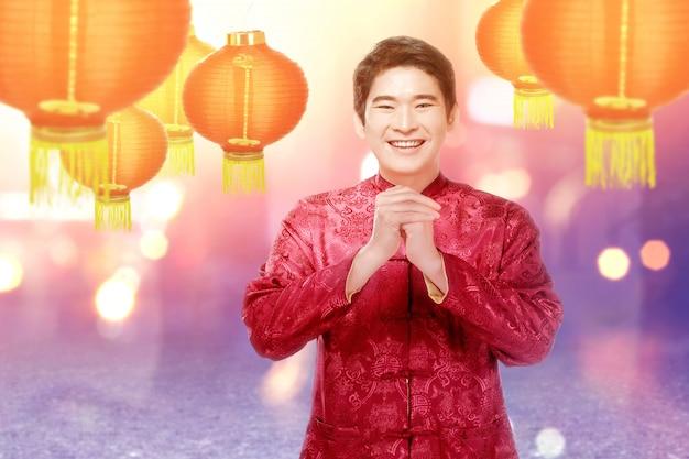 Азиатский китаец в платье чонсам с жестом поздравления