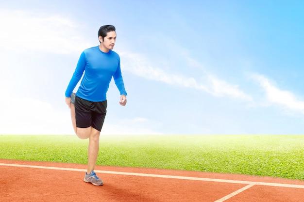 Азиатский бегун раздвигает ноги перед началом бега по беговой дорожке