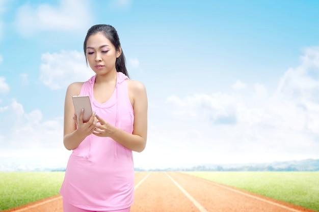 ランニングトラックで実行した後、休憩で携帯電話を使用してアジアのランナー女性