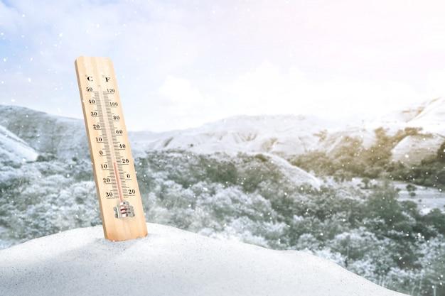 Термометр на снегу для измерения температуры наружного воздуха на фоне ясного неба