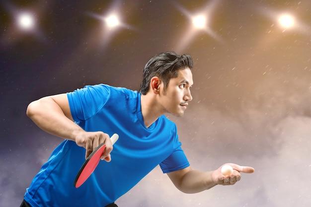 アジアの卓球選手の男がボールを提供