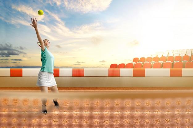 Азиатская теннисистка с теннисной ракеткой и мячом в руках обслуживает мяч