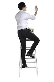 アジア人は梯子の上にペンで何かを書く