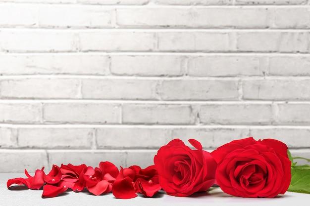 床に赤いバラとバラの花びら