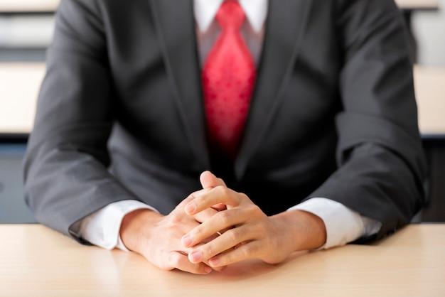 机の上の手で座っている実業家