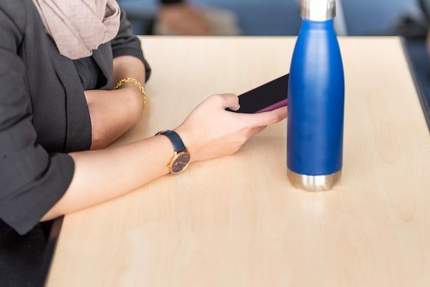 携帯電話を使用しながら机の上に座っている実業家
