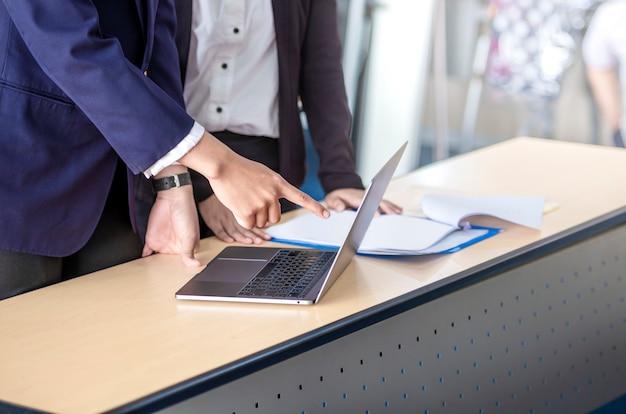 机の上のノートパソコンと一緒に働くビジネス人々