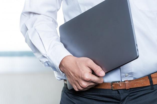 Бизнесмен стоял во время ношения ноутбука