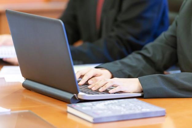 机の上のラップトップを使用してビジネス人々