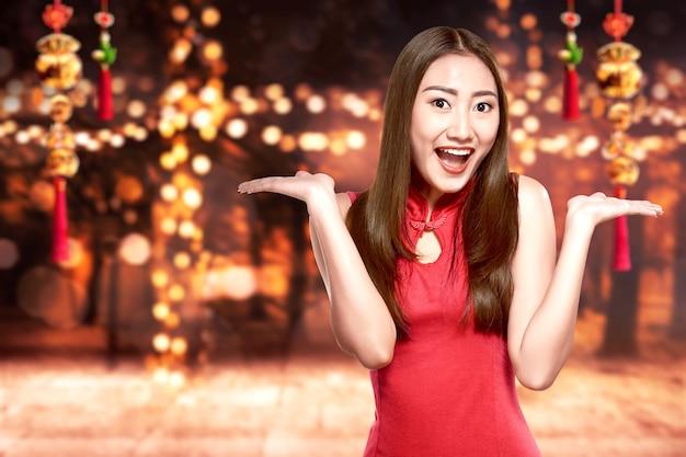 チャイナドレスのアジアの女性は中国の旧正月を祝う