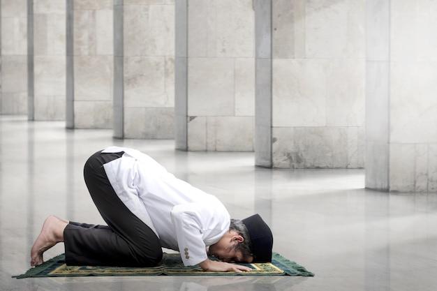 祈りの位置で祈りの敷物を持つアジアのイスラム教徒の男(サラート)