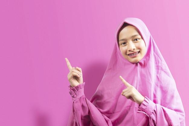 何かを指しているベールのアジアのイスラム教徒の女性