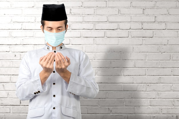 手を上げて祈りながら立っているインフルエンザマスクを身に着けているアジアのイスラム教徒の男性