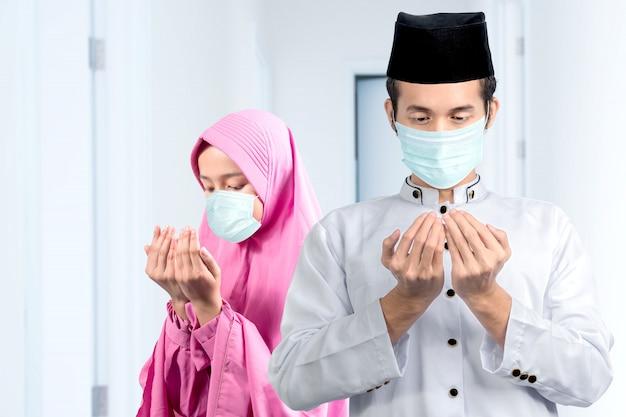 インフルエンザのマスクを身に着けているアジアのイスラム教徒のカップルが手を上げながら立って一緒に祈る