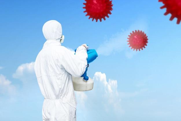 空気中に消毒剤を散布する白い防護服の男