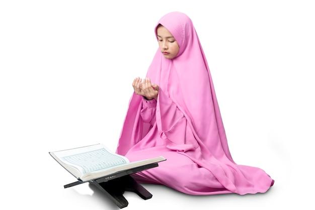 挙手しながら祈りながら座っているベールのアジアのイスラム教徒の女性