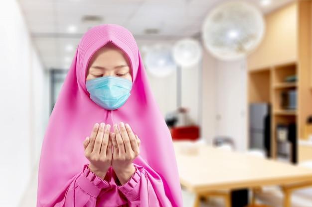 ベールとアジアのイスラム教徒の女性が手を上げて祈りながら立っているインフルエンザマスクを着て