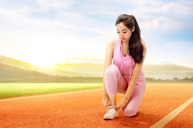 Азиатская женщина бегун, связывая шнурки на беговой дорожке