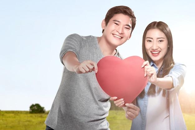 赤いハートを保持しているアジアのカップル