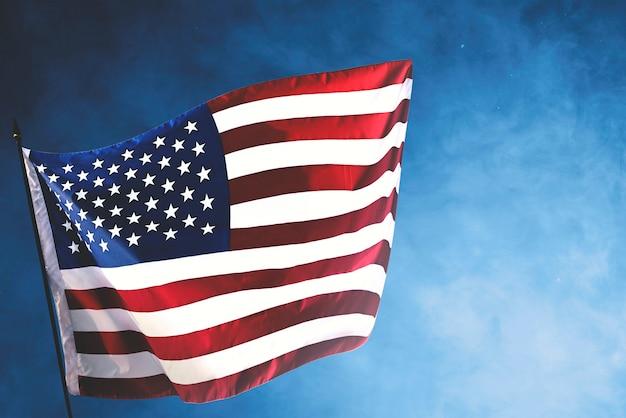 Американский флаг развевается в воздухе с голубым небом