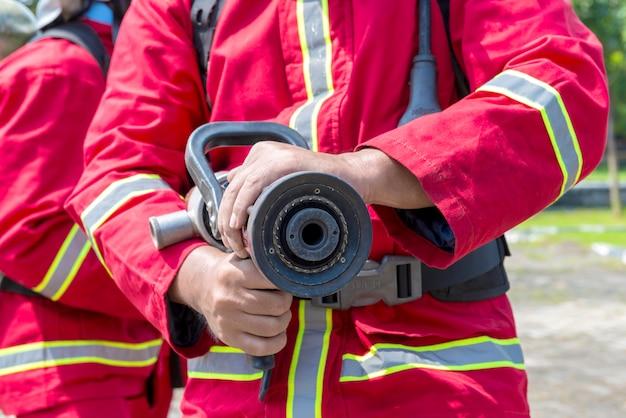 Пожарные в костюме противопожарной защиты, держащие водяной шланг на открытом воздухе