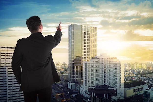 アジアビジネスの男性が空を見ての背面図