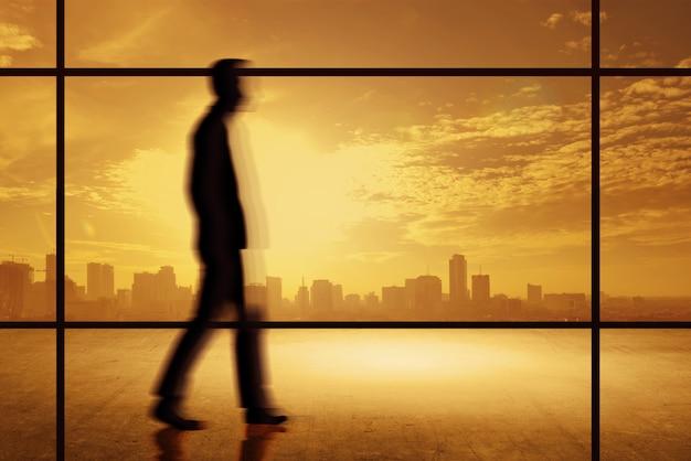 アジアのビジネスマンのモーションブラー効果と一緒に歩いて