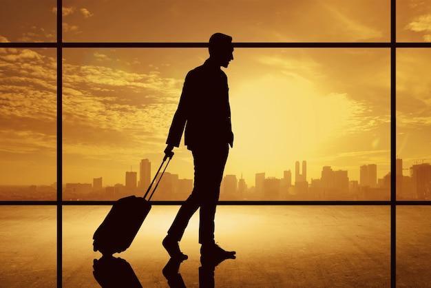 街背景にスーツケースを持って歩くビジネスマンのシルエット