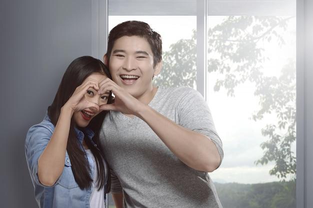 指で心を身振りで示すことで愛の幸せなアジアカップル