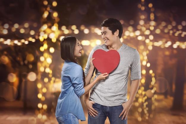 赤いハートを保持している笑顔のアジアカップル
