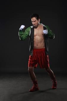 筋肉質のアジアの男性ボクサートレーニングアッパーカットパンチング