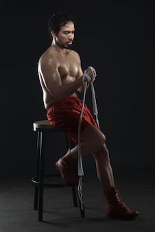 白いストラップを着用しながら椅子に座っているアスリート男アジアボクサー